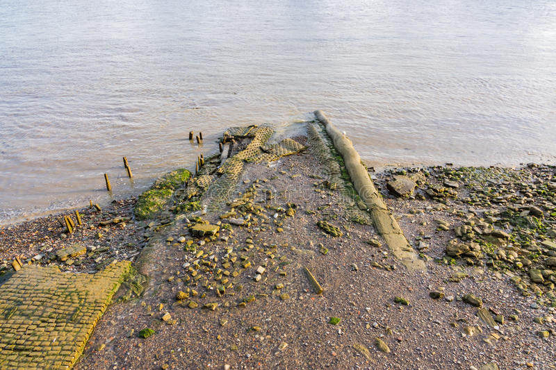 Muddy riverbank at low tide on the River Thames. The low tide reveals the muddy riverbank and old pathways into the River Thames stock images