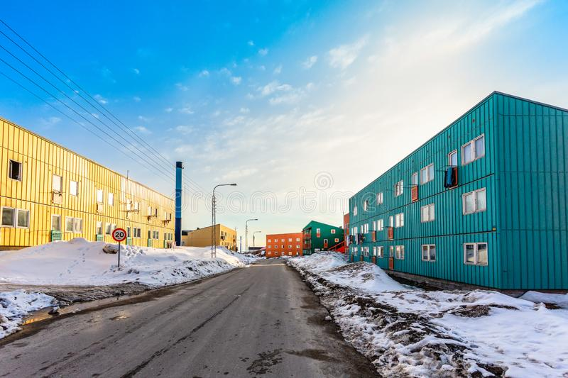 Muddy road with snow and living blocks with long low buildings in  Ilulissat city, Greenland royalty free stock photos