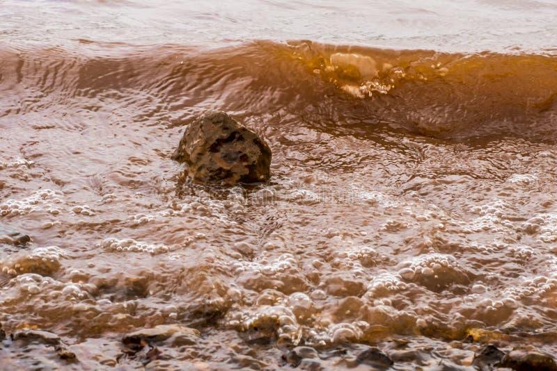 Muddy Water Waves Hitting a Rock, Panshet royalty free stock images