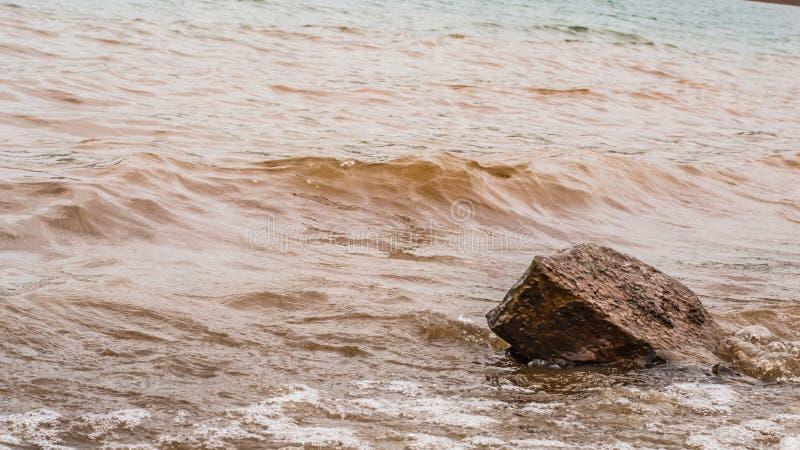 Muddy Water Waves Hitting a Rock, Panshet royalty free stock photo