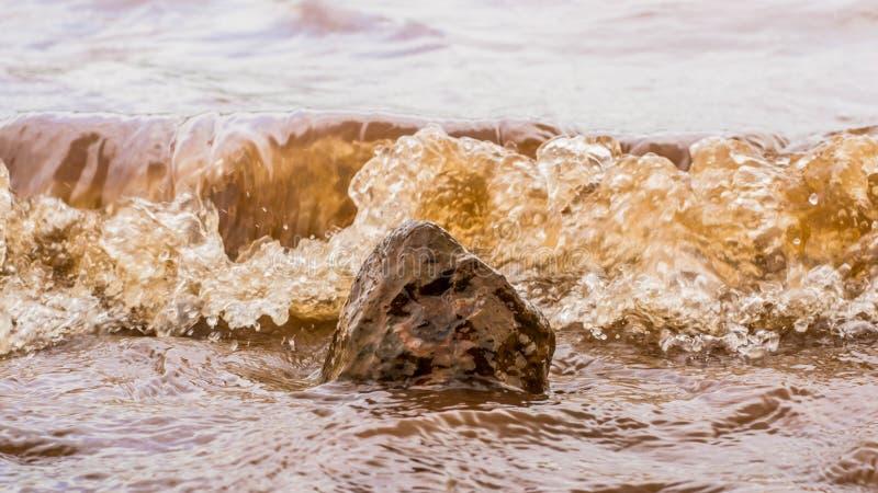Muddy Water Waves Hitting una roca, Panshet imagenes de archivo