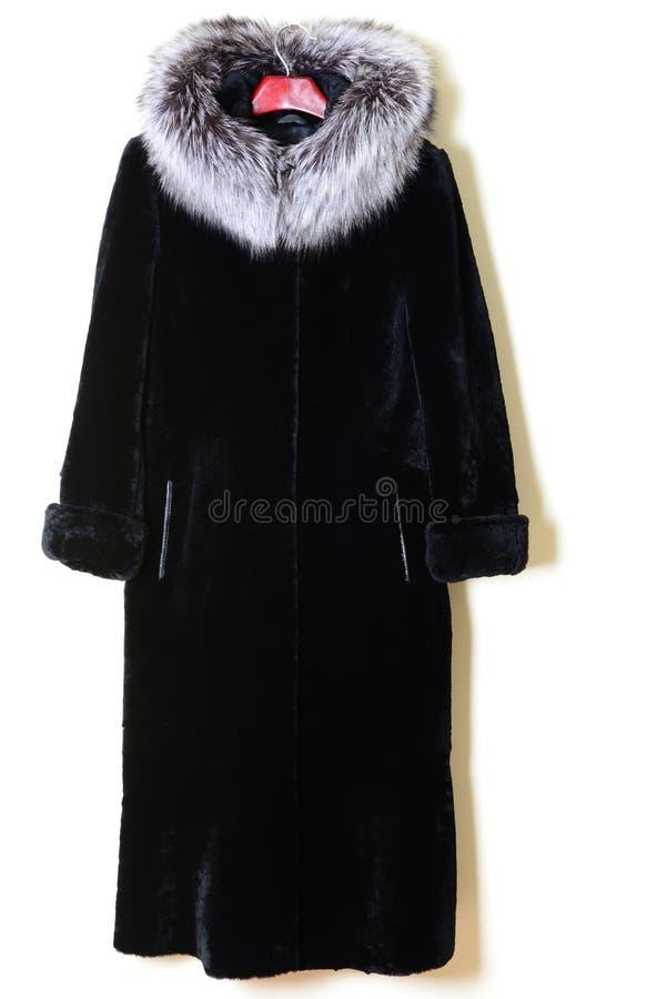 Mudo negro del abrigo de pieles con el cuello de la piel del zorro polar en fondo de la pared Abrigo de pieles en la suspensión imagen de archivo libre de regalías