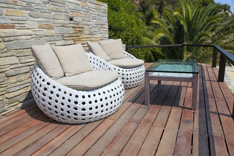 Muebles al aire libre blancos en la terraza de madera del centro turístico imágenes de archivo libres de regalías