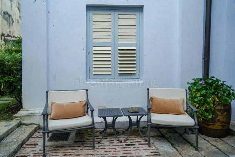 Muebles al aire libre del jardín, sillones grises del metal y tablas laterales delante de la pared azul del edificio con la venta imagen de archivo