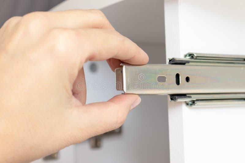 Muebles de junta del conglomerado, guía del rodillo de la tenencia de la mano de un cajón en el tablón blanco fotos de archivo