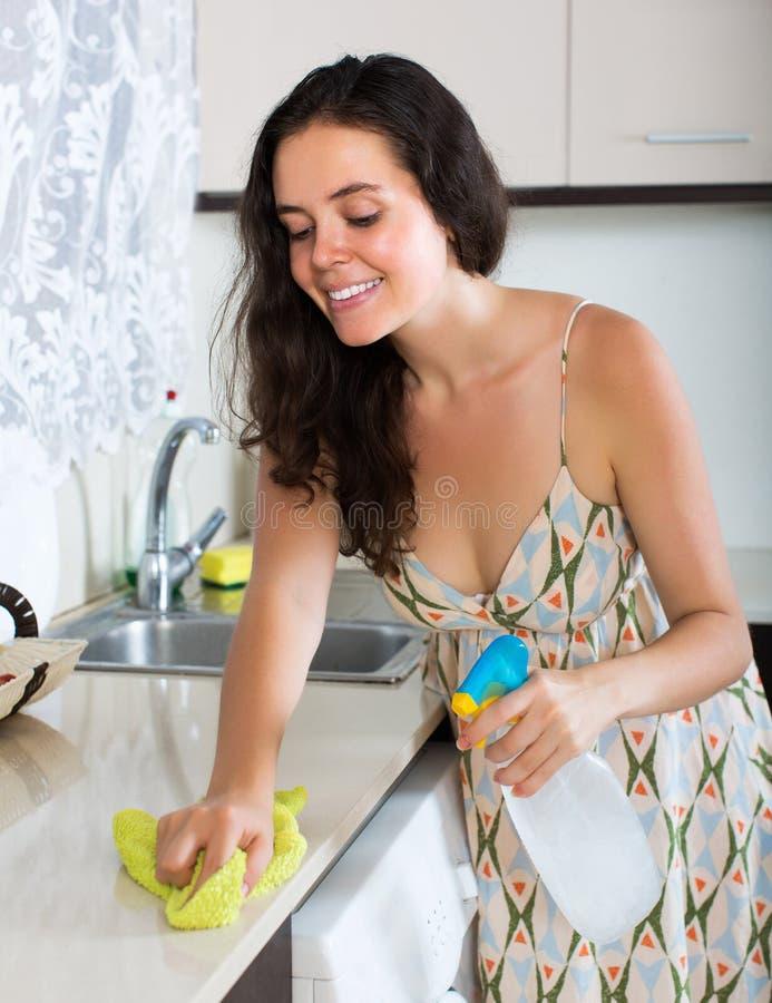 Muebles de la limpieza de la muchacha en cocina fotos de archivo