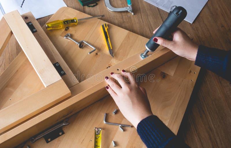 Muebles de madera de la asamblea de la mujer, fijando o reparando la casa con la herramienta del destornillador conceptos vivos m fotografía de archivo libre de regalías