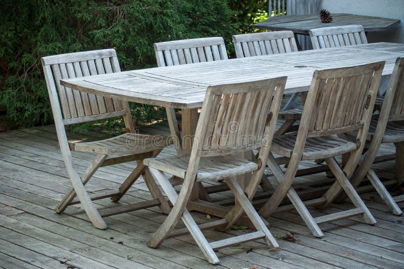 Muebles del jardín de la teca en una terraza de madera en primavera imagen de archivo libre de regalías