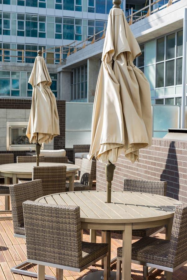 Muebles del patio con los paraguas doblados imagen de archivo