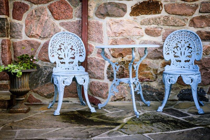 Muebles del patio contra la pared de piedra imagen de archivo libre de regalías