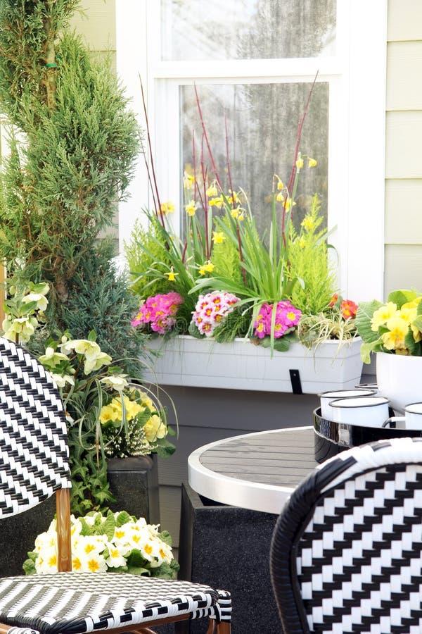 Muebles del patio rodeados por las flores de la primavera imagen de archivo libre de regalías