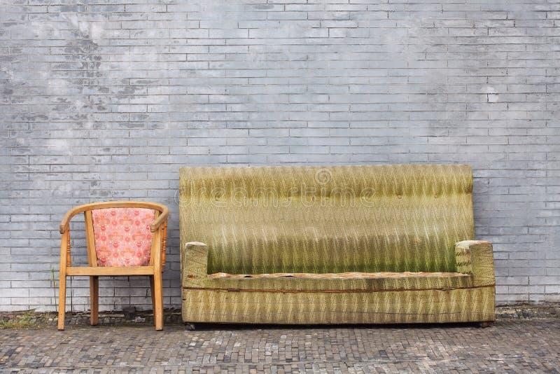 Muebles gastados contra una pared de ladrillo gris, Pekín, China fotos de archivo