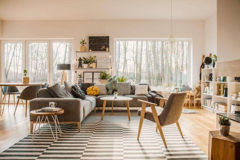 Muebles grises, de madera en un interior espacioso de la sala de estar con w imagen de archivo libre de regalías