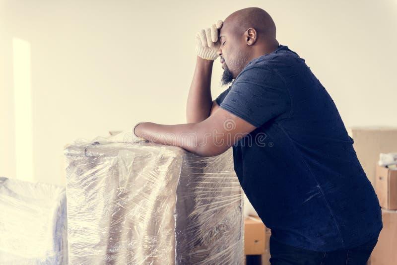 Muebles móviles del hombre negro adentro a la nueva casa fotos de archivo
