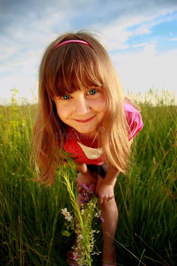 Mueca de la muchacha en un campo fotografía de archivo libre de regalías