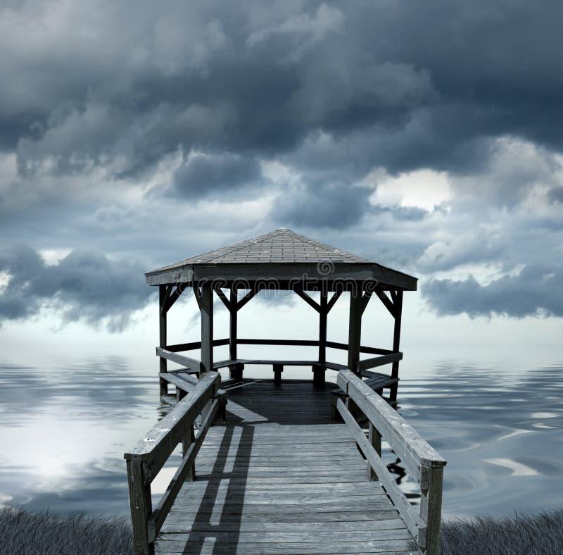 Muelle bajo el cielo tempestuoso imagenes de archivo