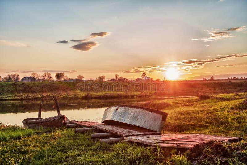 Muelle de madera viejo con los barcos en la puesta del sol fotos de archivo libres de regalías