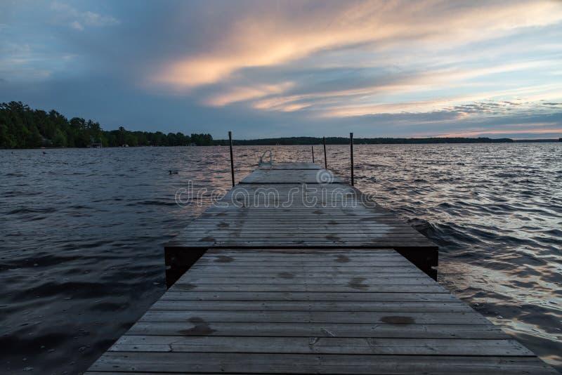 Muelle de Muskoka del lago durante puesta del sol imagenes de archivo