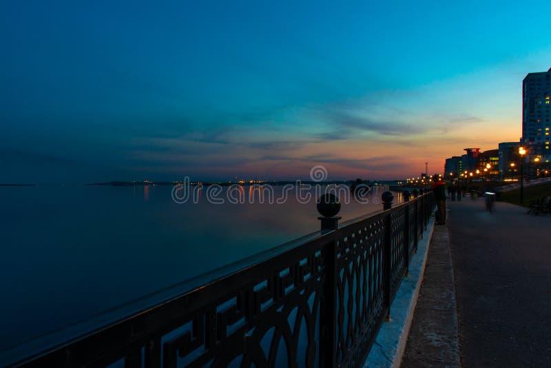 Muelle de Saratov de la ciudad de la noche de la primavera bajo puesta del sol Luces decorativas de la calle y cielo hermoso imagen de archivo