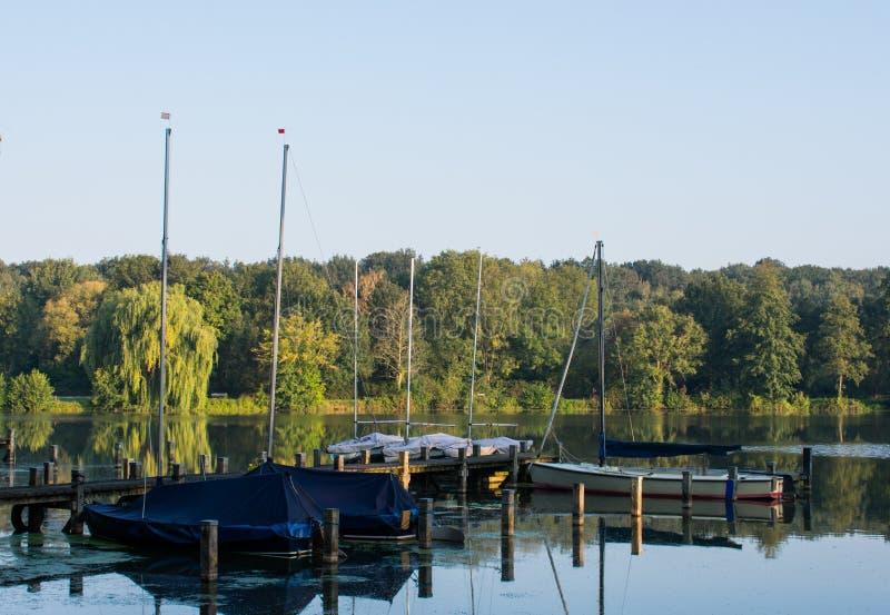 Muelle del barco con los veleros en la madrugada imagen de archivo