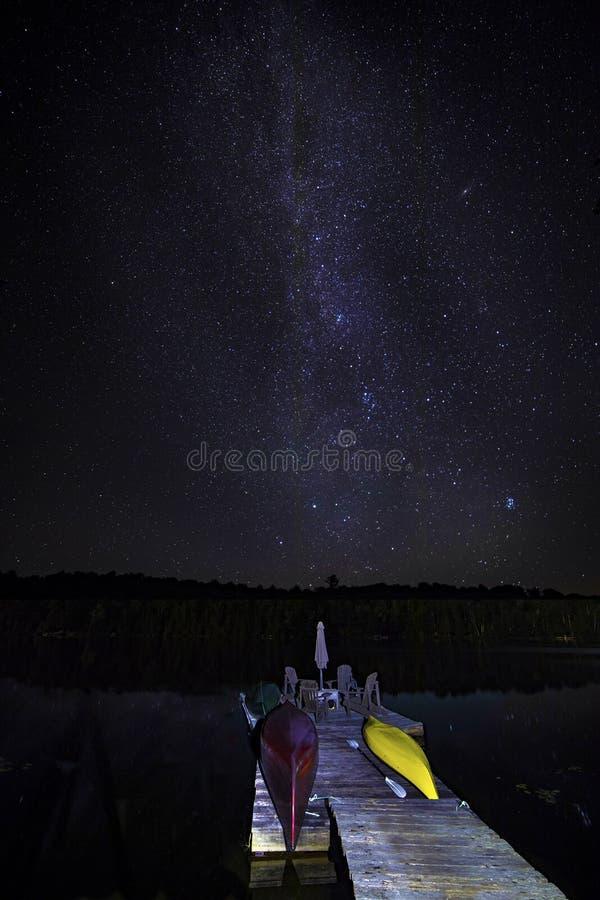 Muelle del barco debajo de un cielo estrellado fotografía de archivo libre de regalías