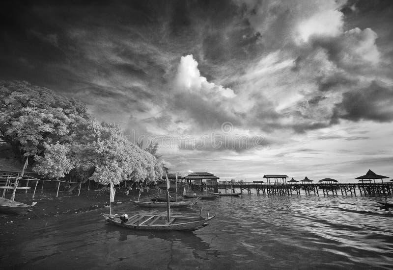 Muelle del barco en la playa debajo del cielo nublado foto de archivo