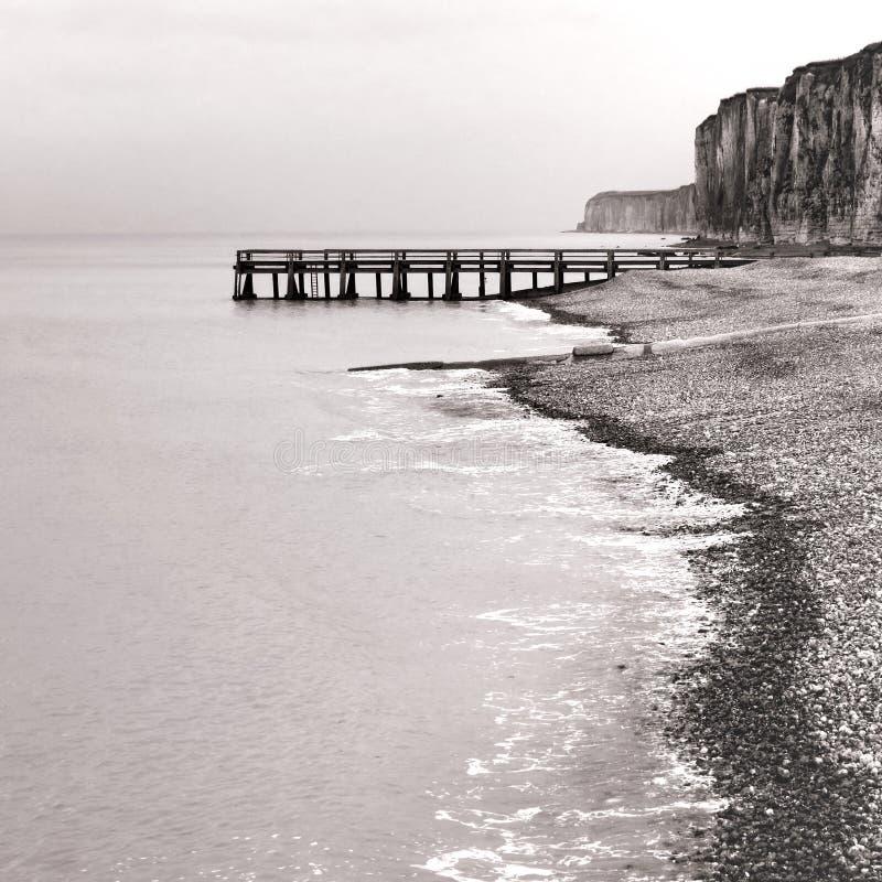 Muelle en el mar y acantilados de Rocky en la playa de la roca de la playa fotografía de archivo