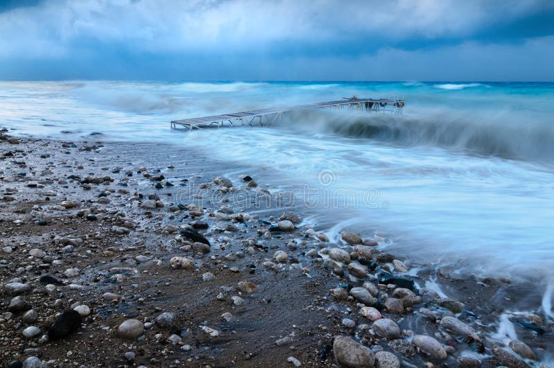 Muelle en la orilla de mar durante un huracán foto de archivo