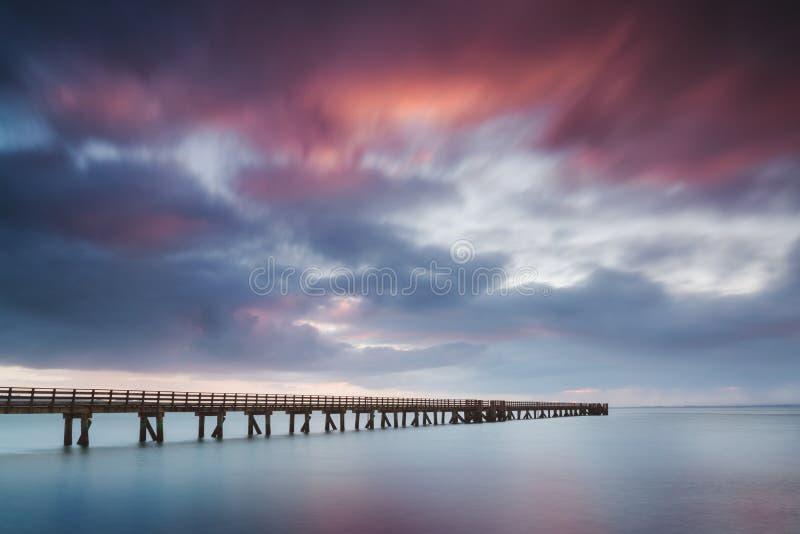 Muelle romántico en Auckland del embarcadero hermoso de Nueva Zelanda en salida del sol con el cielo rosado de la nube Paisaje de imagenes de archivo