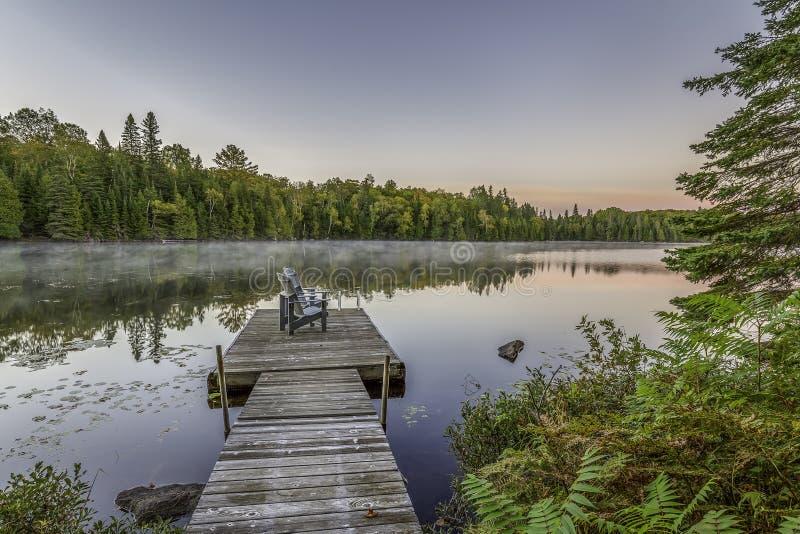 Muelle y sillas en un lago en la puesta del sol fotos de archivo