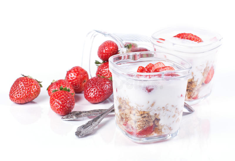 Muesli、草莓和酸奶在白色背景在玻璃 免版税库存图片