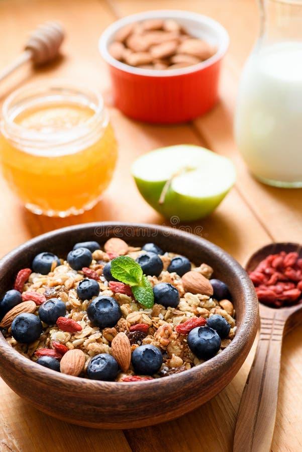 Muesli或格兰诺拉麦片在木碗用蓝莓、goji莓果和杏仁 免版税库存照片