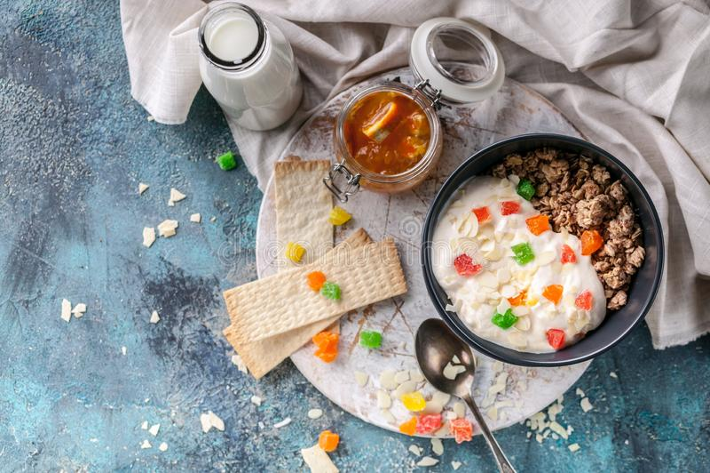 Muesli或格兰诺拉麦片用脯在黑暗的碗、自创酸奶、橙色果酱和牛奶 r 图库摄影