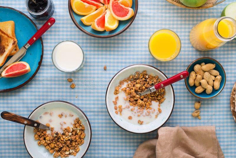 Muesli用酸奶、面包多士、牛奶、橙汁和果子 库存照片