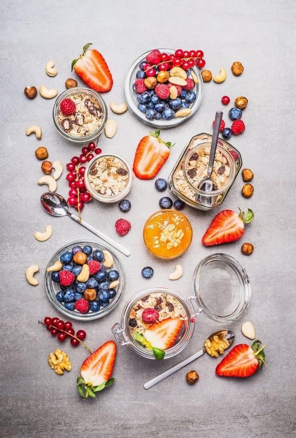 Muesli ή granola στα βάζα, τα φρέσκα μούρα, τους σπόρους και τα καρύδια, τοπ άποψη στοκ εικόνα