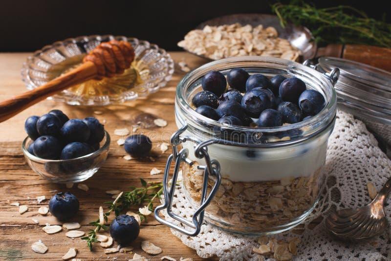 Muesli με το γιαούρτι και μπλε μούρα στο βάζο γυαλιού στοκ εικόνες