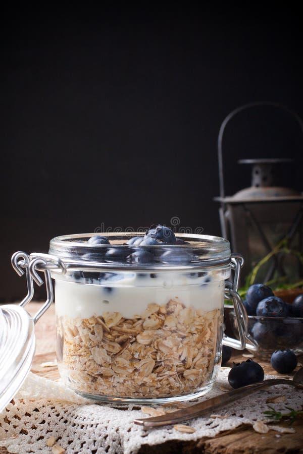Muesli με το γιαούρτι και μπλε μούρα στο βάζο γυαλιού στοκ φωτογραφία