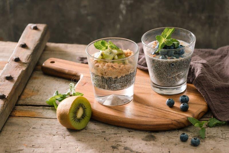 健康早餐-碗muesli、莓果和果子,坚果,猕猴桃,牛奶 免版税库存照片