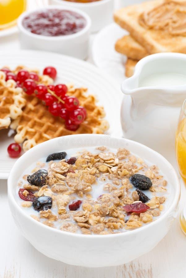 Muesli avec du lait, gaufres avec des baies, pain grillé, confiture pour le petit déjeuner photos libres de droits