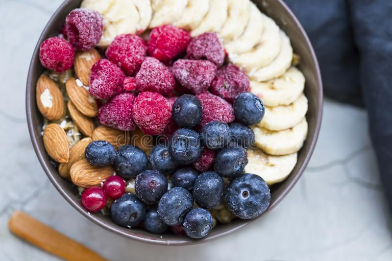 Muesli bowl with berries, banana and almonds, oatmeal breakfast bowl top view with berries stock image