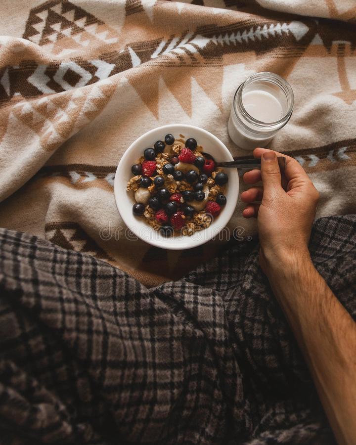 Muesli in bowl with hand stock photography