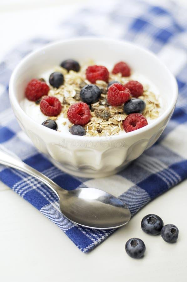 Muesli. Bowl with oatflakes,raisins,fruits and yoghurt, Selective focus stock photo