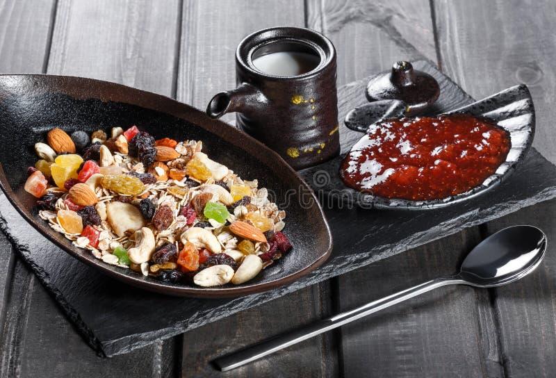 Muesli bowl with yogurt, granola, sliced banana, cashew, almonds, cranberries, nuts, dried fruits mix on dark wooden table stock image