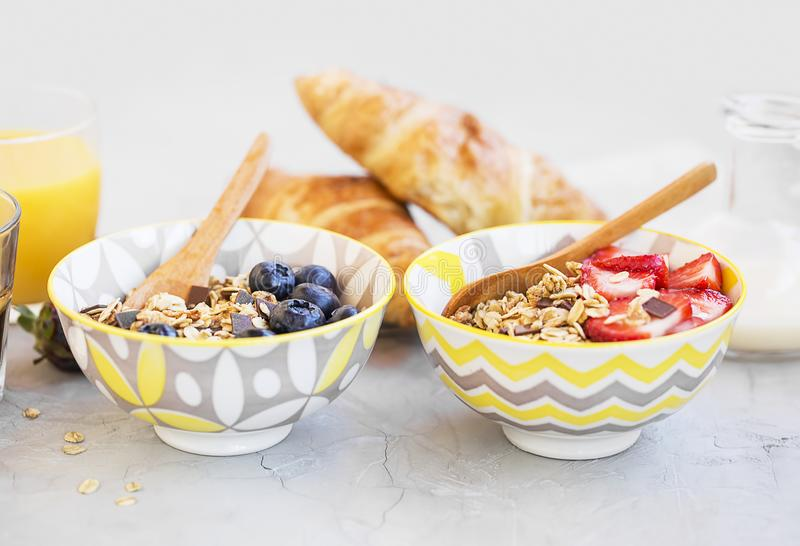 Muesli bowls with strawberries, blueberries fruits and milk , he royalty free stock photo