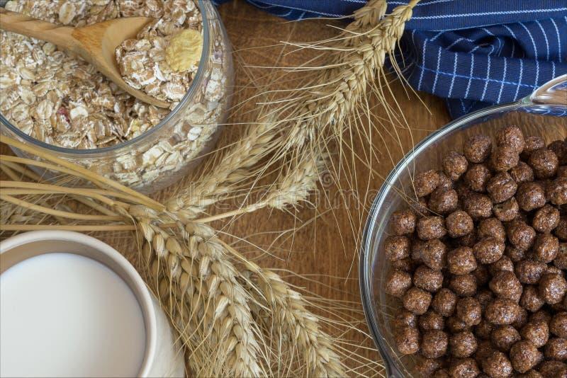 Muesli, céréale de petit déjeuner, farine d'avoine dans un récipient en verre et une tasse de lait sur une table en bois Nourritu photographie stock libre de droits
