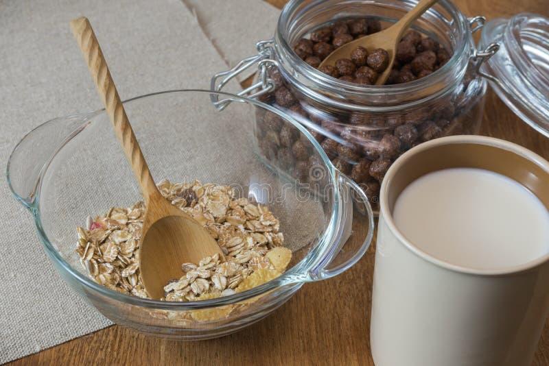 Muesli, cereal de desayuno, harina de avena en un envase de cristal y una taza de leche en una tabla de madera Alimento rústico imagen de archivo
