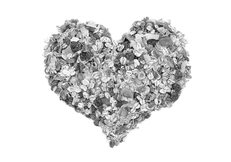 Muesli cereal grains, seeds, fruit and nut heart. Muesli cereal grains, seeds, fruit and nut in a heart shape, isolated on a white background - monochrome royalty free stock photography
