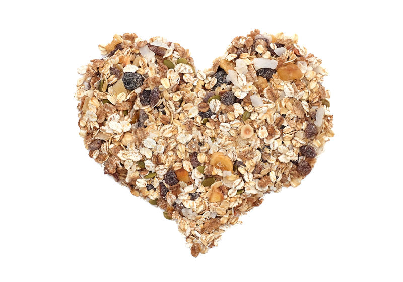 Muesli cereal grains, seeds, fruit and nut heart. Muesli cereal grains, seeds, fruit and nuts in a heart shape, isolated on a white background royalty free stock image