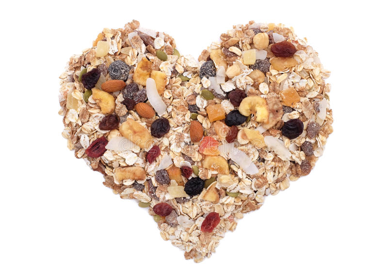 Muesli cereal, seeds, mixed fruit and nuts heart. Muesli - cereal flakes with seeds, mixed fruit and nuts - in a heart shape, isolated on a white background royalty free stock photography