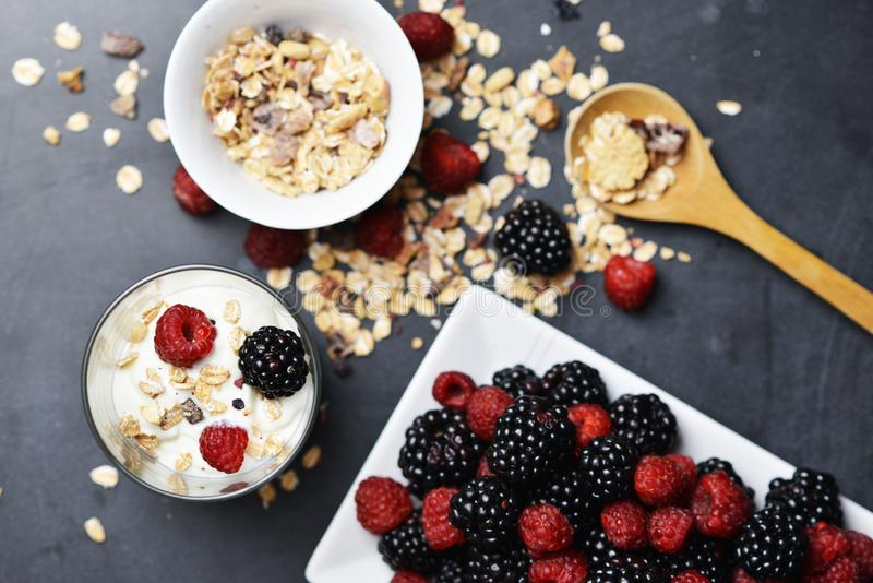 Muesli cereals, yogurt and fresh berries on dark background, preparing a healthy and delicious breakfast with natural ingredients stock photo